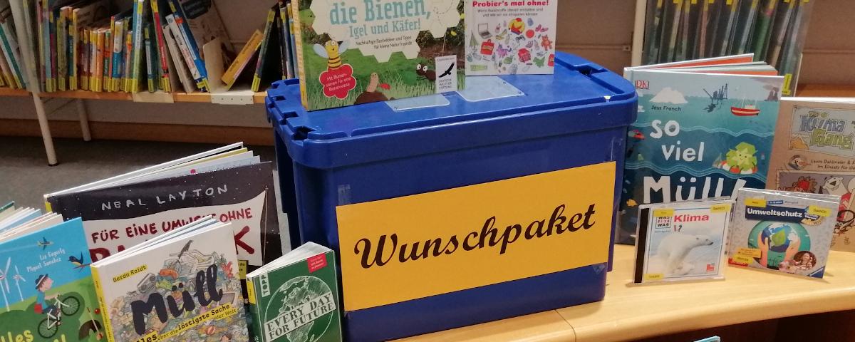 Blaue Kiste mit der Aufschrift Wunschpaket, darum Bücher und CDs zum Thema Müll