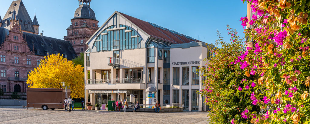 Außenansicht der Stadtbibliothek vom Marktplatz aus, an der rechten Seite sind lila blühende Blumen zu sehen, auf der linken Seite ein gelber Herbstbaum