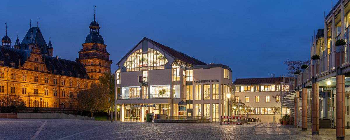 Beleuchtete Stadtbibliothek bei Nacht vom Marktplatz aus. Links daneben sieht man das Schloss und rechts einen Teil der Stadthalle.