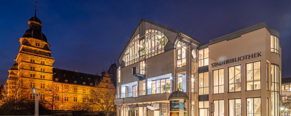 Aufnahme der beleuchteten Stadtbibliothek bei Nacht, im Hintergrund sieht man das Aschaffenburger Schloss.